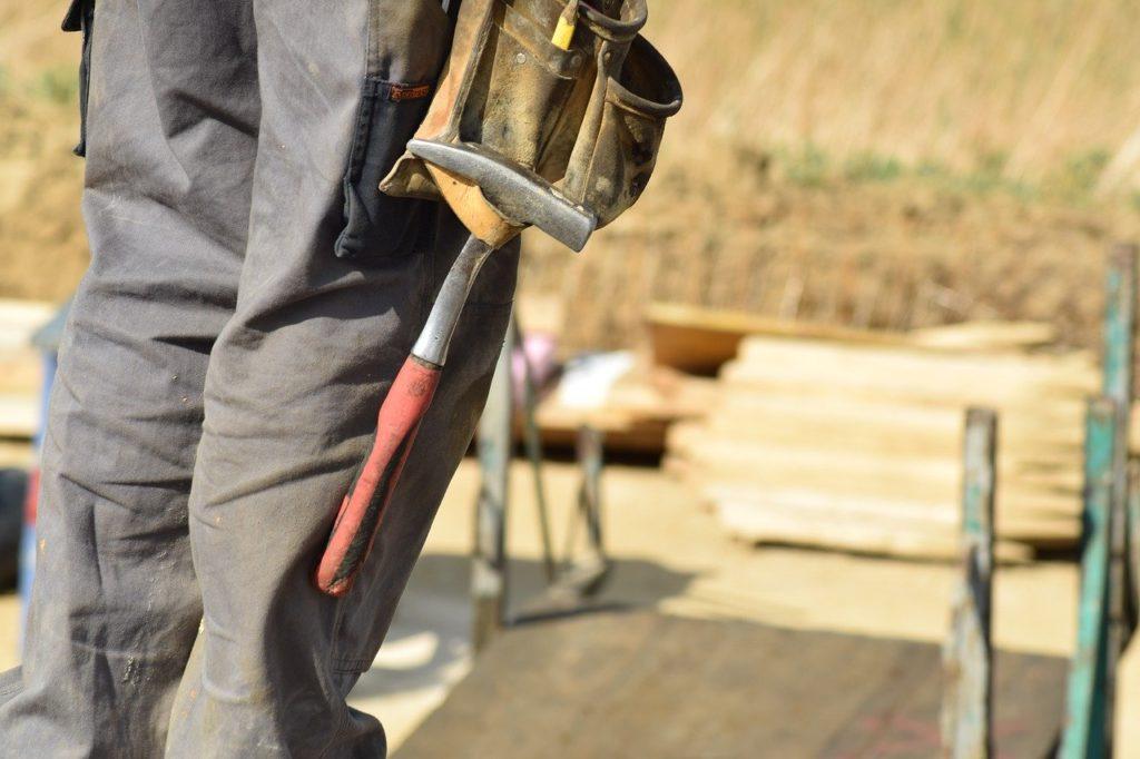 Tømrer med hammer i beltet som står på en byggeplass, tømrerfirma Ski og Follo